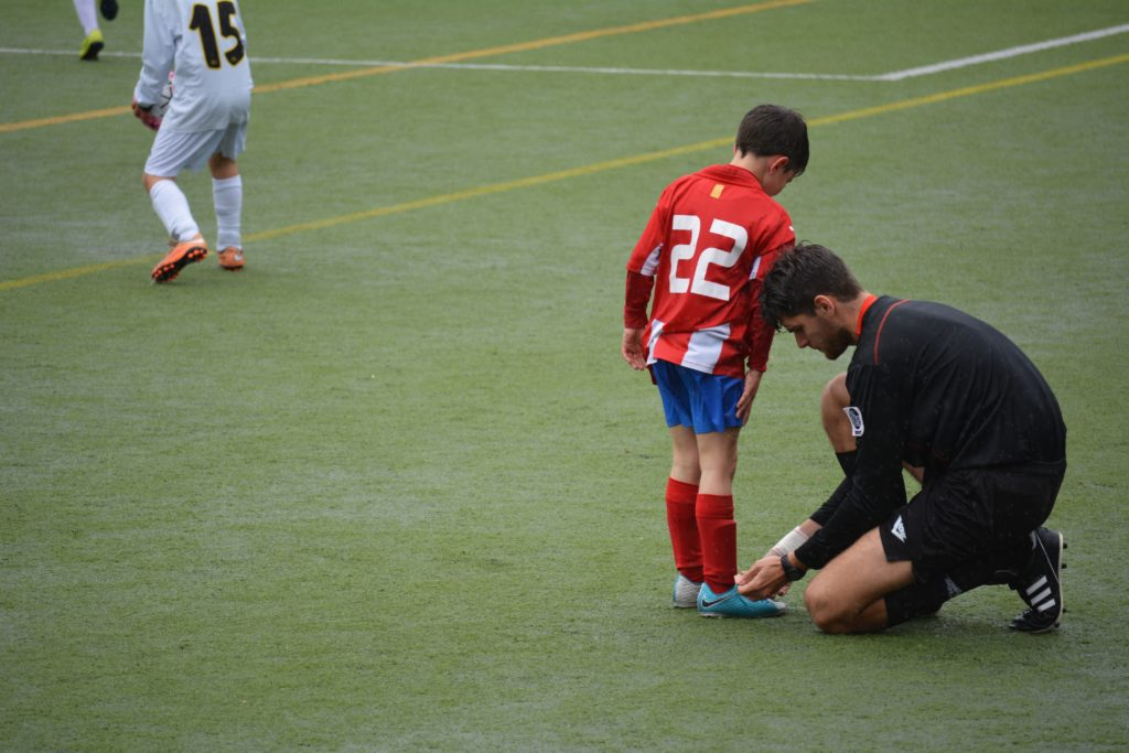 A photo of a football coach helping a young player to tie his laces